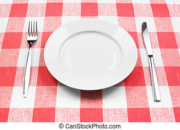 Messer, weißer Teller und Gabel auf rot geprüftem Tischtuch
