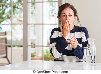 Mitten im Alter trinkt eine Frau ein Glas Wasser-Bedecken Mund mit Hand schockiert vor Scham aus Versehen, Ausdruck der Angst, Angst in Stille, Geheimkonzept.