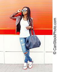 Mode-Afrikanische Frau mit Tasche in der Stadt über rotem Hintergrund.
