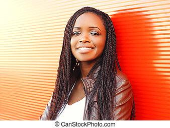 Mode lächelnde Afrikanerin in der Stadt über rotem Hintergrund.