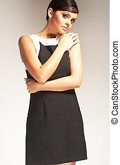 Modemodell mit Lichthintergrund im schwarzen Kleid