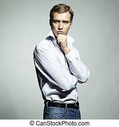 Modeportrait eines jungen, schönen Mannes auf weißem Hintergrund