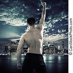 Muskel-Athlet über der Stadt.