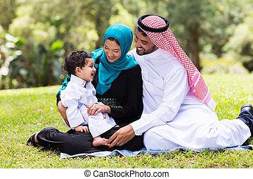 Muslimische Familie sitzt draußen.