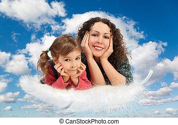 Mutter mit Tochter auf der Feder auf weiß, flauschige Wolken im blauen Himmel kollabieren