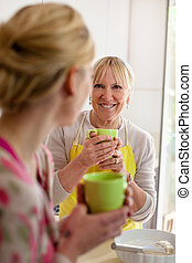 Mutter und Tochter reden, trinken Kaffee in der Küche.