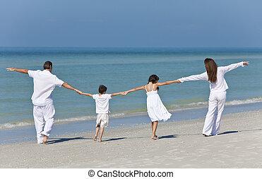Mutter, Vater und Kinder halten Händchen am Strand