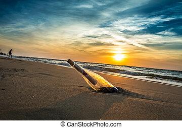 Nachricht mit Brief in der Flasche an einem Strand in Sonnenuntergang.