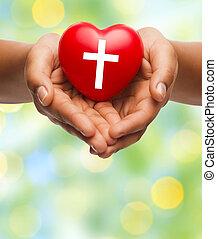 Nahe der Hände, die Herz mit Kreuzsymbol halten.
