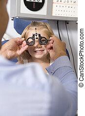 Optiker im Untersuchungsraum mit einem jungen Mädchen im Stuhl lächelnd
