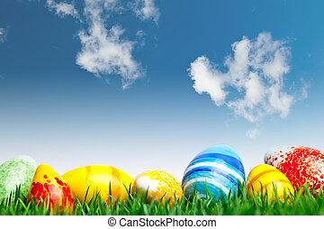 Ostereier im grünen Gras über dem blauen Himmel mit Wolken