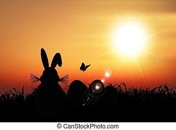Osterhase saß im Gras gegen einen Sonnenuntergang.