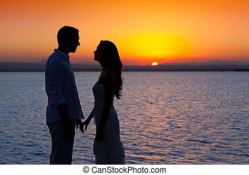 Paar verliebte, leichte Silhouette am Sonnenuntergang am See