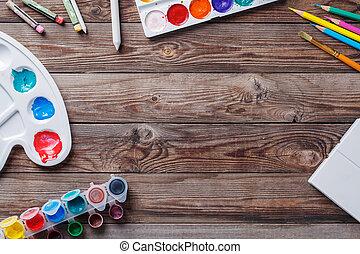 Papier, Aquarelle, Pinsel und Kunstsachen auf Holztisch