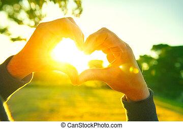 Person, die Herz mit Händen über die Natur Sonnenuntergang Hintergrund. Silhouette Hände in Herzform mit Sonne innen