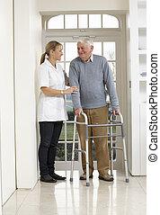 Pfleger, die älteren Männern helfen, sich zu bewegen