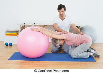 Physische Therapeutin, die Senioren mit Yoga-Ball unterstützt.