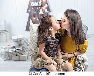 Porträt einer Mutter, die eine Tochter küsst.