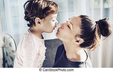 Porträt einer Mutter, die ihr geliebtes Kind küsst.