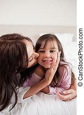 Porträt einer Mutter, die ihre Tochter küsst
