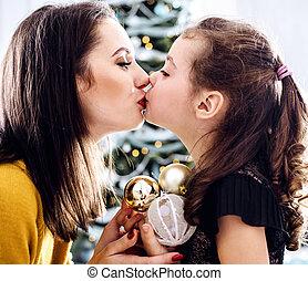 Porträt einer Mutter, die ihre Tochter mit Glaskugeln küsst.