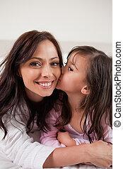 Porträt eines Mädchens, das ihre Mutter küsst
