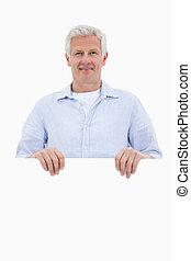 Porträt eines reifen Mannes, der hinter leerem Brett steht
