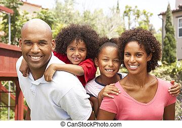 Portrait der glücklichen Familie im Garten