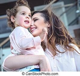 Portrait einer fröhlichen Mutter, die geliebtes Kind kuschelt.