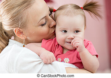 Portrait einer fröhlichen Mutter, die ihre Tochter zu Hause küsst.