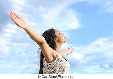 Portrait einer schönen arabischen Frau atmen frische Luft mit erhobenen Armen.