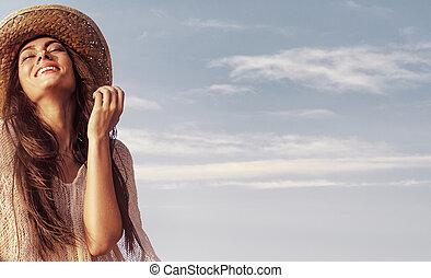 Portrait einer schönen Frau, die das Sommerwetter genießt.
