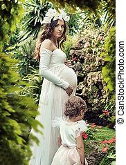 Portrait einer schwangeren Frau, die mit ihrem Kind posiert.