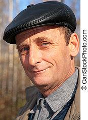 Portrait eines älteren Mannes mit schwarzem Hut im Herbst.