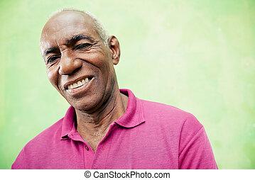 Portrait eines älteren Schwarzen, der auf die Kamera schaut und lächelt