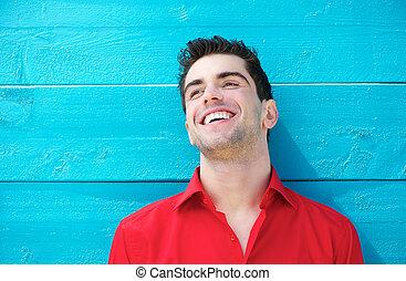 Portrait eines hübschen jungen Mannes, der draußen lächelt.