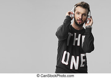 Portrait eines hübschen jungen Mannes, der Musik vor grauem Hintergrund hört.