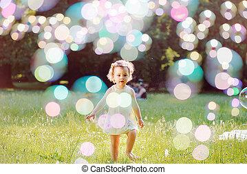 Portrait eines kleinen Mädchens, das Seifenblasen spielt.