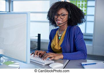 Portrait eines lächelnden Kundenservice-Vertreters mit einem afro am Computer mit Headset.