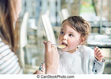 Portrait eines süßen Babys, das von ihrer Mutter gefüttert wird.