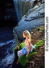 Portrait eines wunderschönen Mädchens, das an der Schwelle der Flusswasserfälle am frühen Sommermorgen Schönheit der Natur genießt