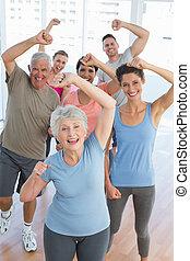 Portrait von lächelnden Menschen, die Fitnessübungen machen.