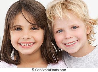 Portrait von zwei glücklichen Kindern in der Küche