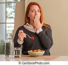 Redhead-Frau isst Obstschale, Kiwi und Erdbeere in der Hausdecke Mund mit Hand geschockt vor Scham für Fehler, Ausdruck der Angst, Angst in Stille, geheime Konzept.
