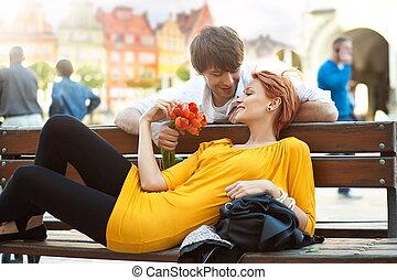 Romantisches junges Paar entspannt sich draußen und lächelt