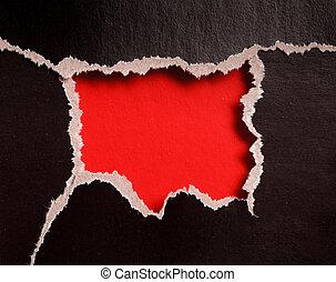 Rotes Loch mit zerrissenen Kanten in schwarzem Papier