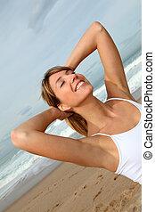 Schöne Frau atmet frische Luft am Strand.