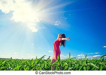 Schöne Frau auf dem Sommerfeld, die Hände über den blauen, klaren Himmel erhebt. Glückliche junge, gesunde Frau, die die Natur im Freien genießt