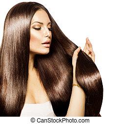 Schöne Frau, die ihr langes und gesundes braunes Haar berührt