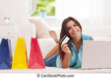 Schöne Frau, die mit Kreditkarte bezahlt, um zu Hause einzukaufen